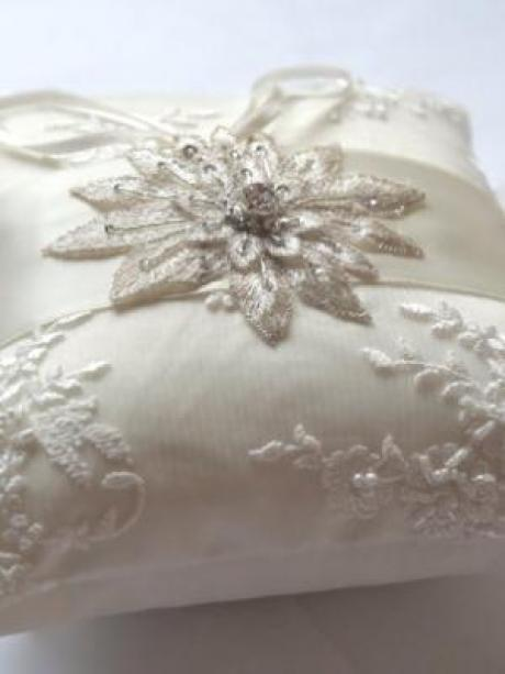 An ivory beaded lace wedding ring pillow with rhinestone detail in the shape of a star for a wedding.