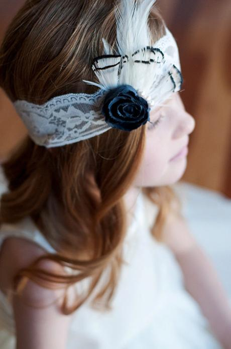 A 7 year old girl wearing an ivory lace elasticated headband with a black flower and feather trim.