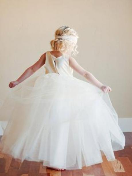 A 5 year old girl showing the back of an ivory flower girl dress. The dress has a full tulle skirt and a cotton bodice.