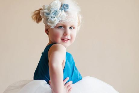 A side view of a girl wearing  peacock blue silk and tulle flower girl dress with a lace headband with organza and silk flowers.