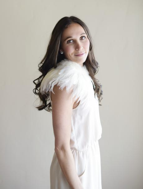 A bridesmaid wearing an ivory feather wedding shawl at a wedding with flower girls in ivory flower girl dresses.