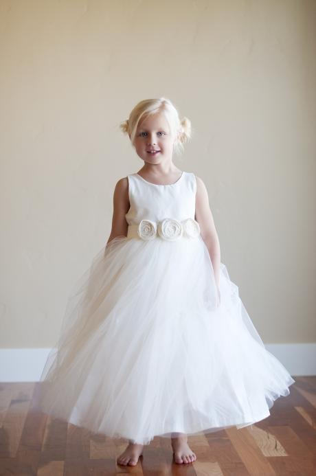 A girl wearing an ivory flower girl dress with a tulle and cotton skirt and a flower belt. £89.50