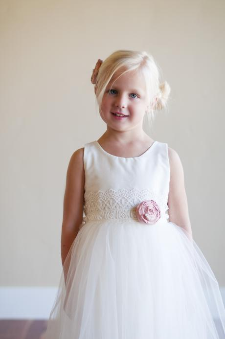 A young bridesmaid wearing a tulle flower girl dress with a cotton skirt, wide lace belt and pink silk flower.