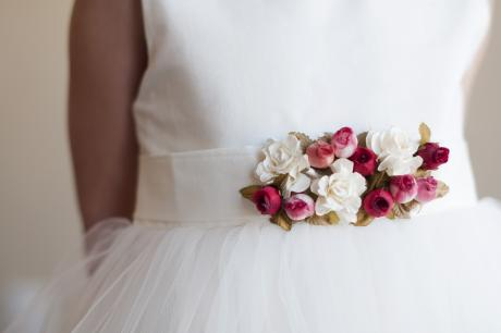 A close up of a flower girl dress with a sash with pink, red and white flowers.