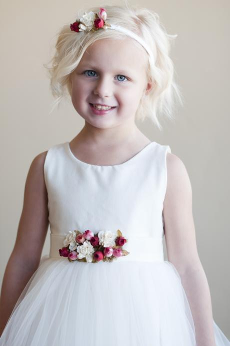 A 6 year old girl wearing an ivory flower girl dress with tulle skirt and pink, red and ivory roses on the belt.