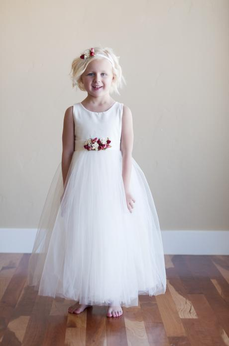 A young girl wearing a flower girl dress with red, pink and ivory flowers. The dress is cotton and has a tulle skirt.
