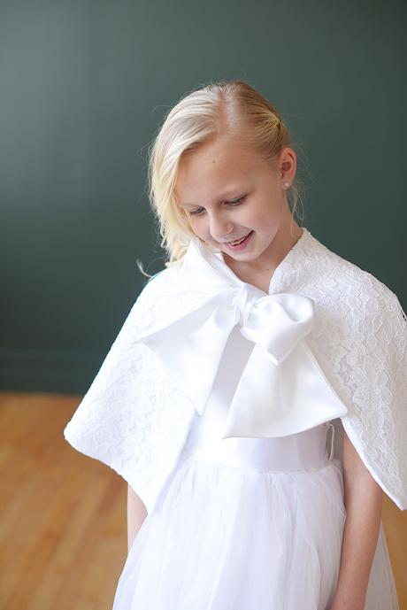 A young girl at First Communion wearing a white, silk dress and a lace cape with big bow.