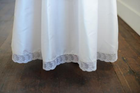 A close up of a lace hem on a white communion dress
