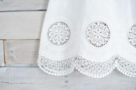 A close up of a ham of an ivory lace christening gown handmade in London.