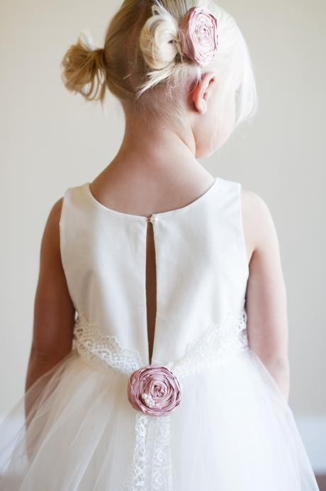 A young flower girl wearing a bespoke lace junior bridesmaid dress with a lace belt and pink silk flower.