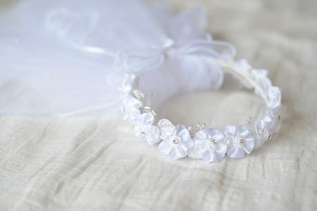 A close up of a first communion veil and crown with a beaded crown with flowers.