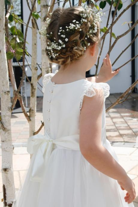 Toddler flower girl holding a basket of flowers and wearing a silk, lace and tulle flower girl dress.