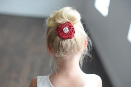A red flower girl hair accessory with diamanté embellishment