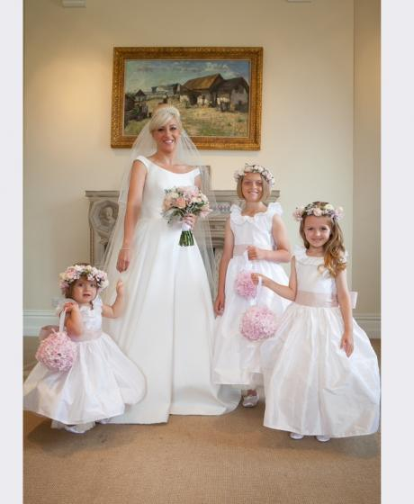 A group of flower girls, junior bridesmaids and a bride wearing floor length, ivory silk flower girl dresses and holding blush pink floral flower girl baskets.