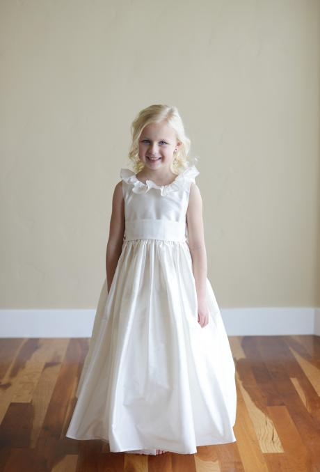 A girl at a wedding wearing a made to measure ivory silk flower girl dress and junior bridesmaid dress with ruffled collar made in the UK.