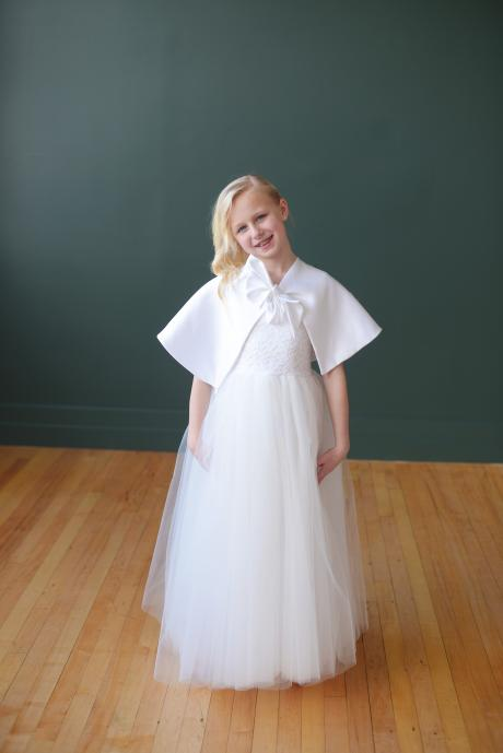 A girl wearing a First Communion tulle dress and white satin first communion cape which ties in a bow at the front.