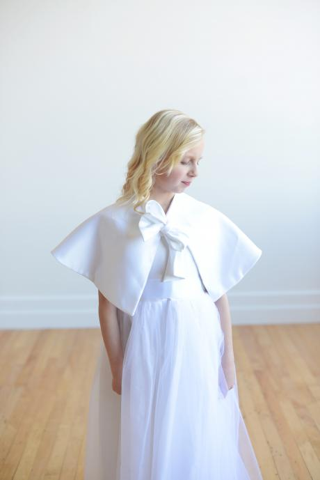 A flower girl wearing a satin dress and First Communion cape to keep warm