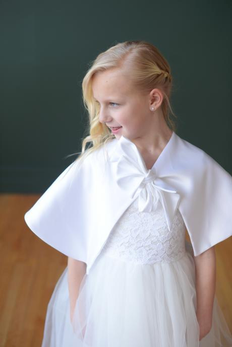 A girl wearing a white satin first communion cape which ties with a big bow