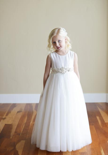 A pretty young girl wearing a sequin flower girl or junior bridesmaid dress with sequin motif on the sash.