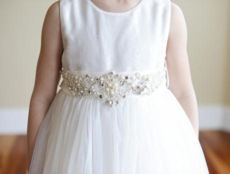 A close up of a girl in an ivory flower girl dress with a diamanté motif on the sash.