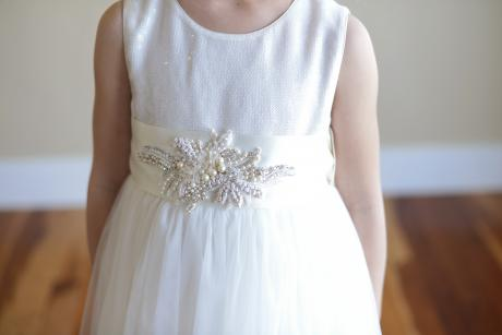 A close up of a little girl wearing a white diamanté sash on a sequin flower girl dress.