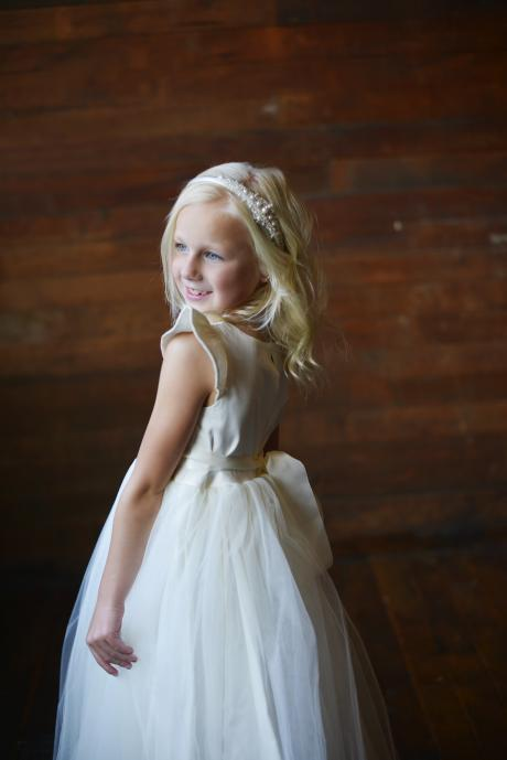 A side view of a bespoke flower girl dress in ivory with wide ribbon sash and butterfly sleeves.