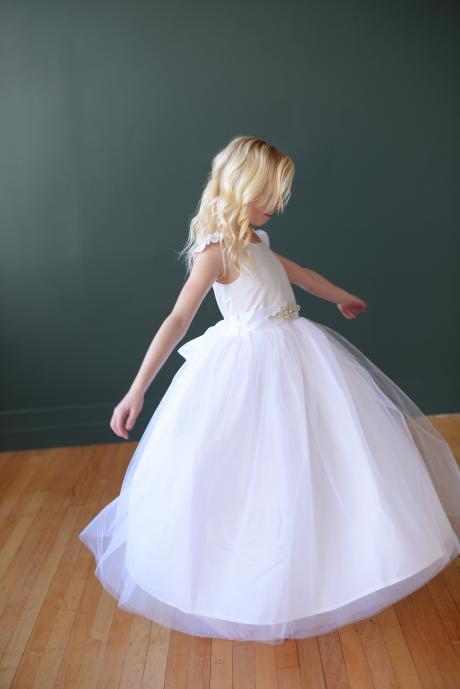 A flower girl wearing a silk dress with sleeves, sash with pretty diamanté motif and tulle skirt.