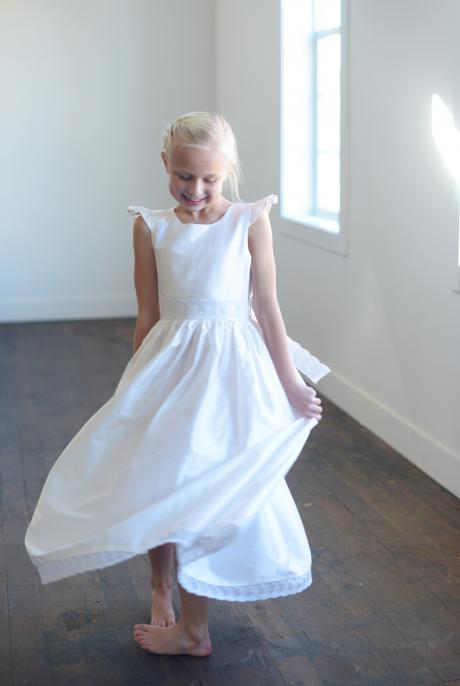 A girl twirling whilst wearing a white silk and lace first communion dress