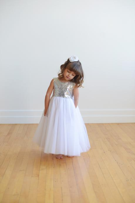 A flower girl wearing a silver sequin flower girl dress with a big bow and a full tulle skirt