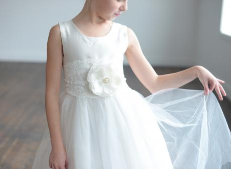 A young flower girl wearing a white first communion and flower girl dress with a big flower on an elasticated lace belt.