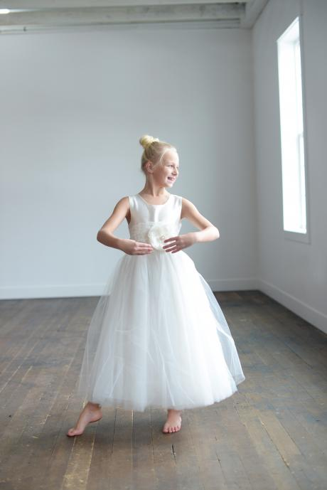 An 8 year old girl wearing a ballerina length first communion dress in white with a lace belt and a full tulle skirt.