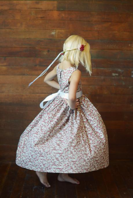A girl twirling and wearing a strawberry pint flower girl dress