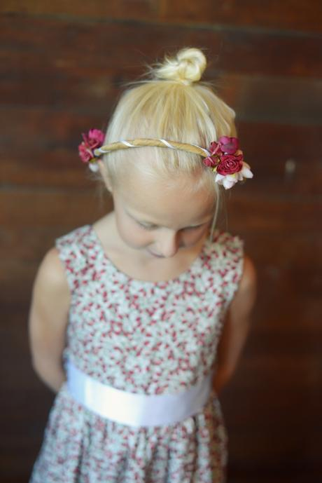 A girl in a strawberry print dress with a satin bow and a hair crown
