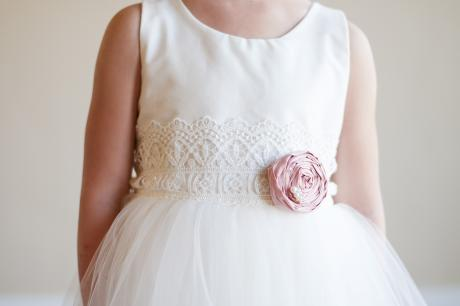 A girl wearing a made to measure flower girl dress in ivory cotton with a pink silk flower on a lace sash.
