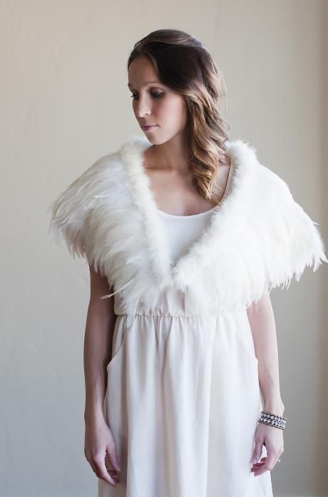 A front view of a bride at a wedding wearing an ivory feathered wedding wrap which fits over her shoulders.