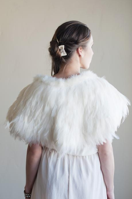 The back of an ivory, feathered bridal shawl for brides which is fitted over the shoulders.