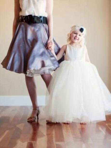 A girl standing holding a lady's hand wearing an ivory tulle flower girl dress with oversized tulle skirt.