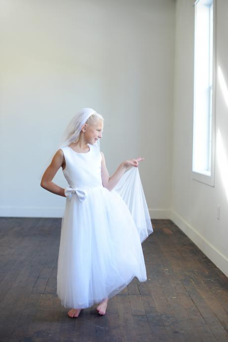 A girl wearing a white first communion dress in white satin matched with a tulle veil with diamanté trim