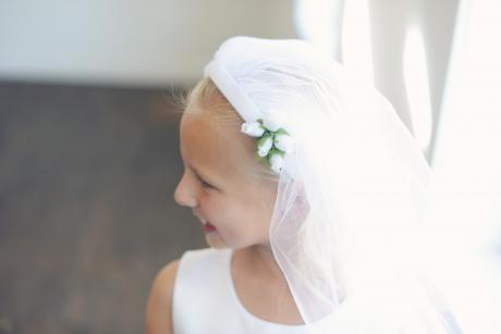 A girl wearing a handmade white First Communion veil with flower embellishment