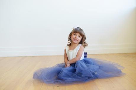 A little flower girl sitting on the floor wearing a blue and white tulle flower girl dress or junior bridesmaid dress. The bodice has  daimante trim.