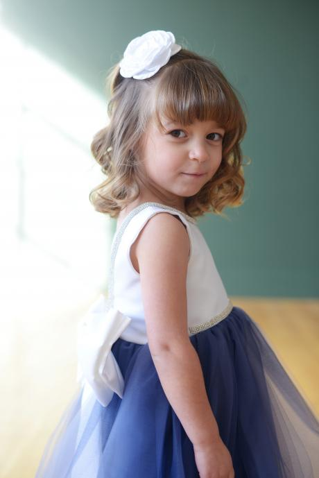 A side view of a blue and white flower girl dress with a white satin bodice and a big bow with diamante trim.