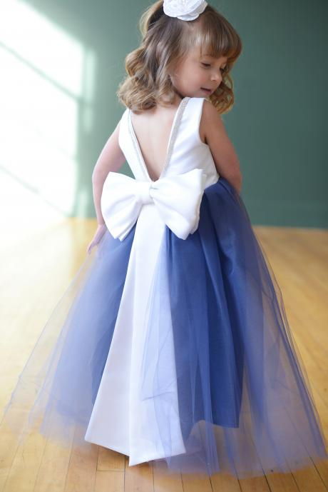 A little flower girl wearing a blue tulle flower girl dress with white satin bodice which has a v neck and diamante trim