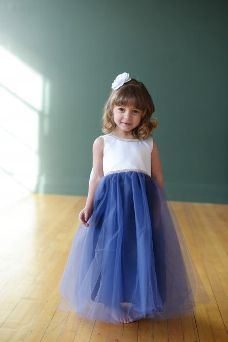 A toddler flower girl at a wedding wearing a diamante and white flower girl dress with a blue tulle skirt.