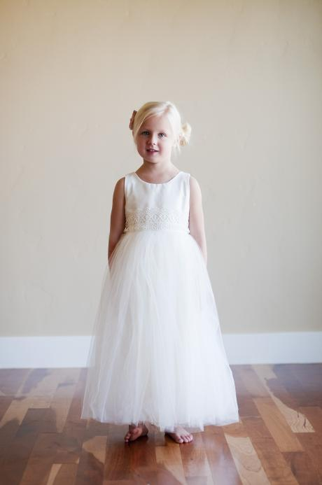 A young flower girl wearing a hand made tulle, lace and cotton dress with a silk flower embellishment.