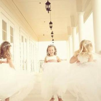 Three young bridesmaids on a balcony wearing ivory tulle flower girl dresses and red sashes.