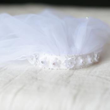 A close up of a white first communion veil with a double veil and beaded flowers on the headband