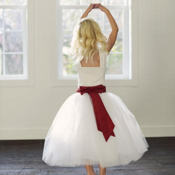 A flower girl at a wedding wearing a white and red tutu skirt in a ballerina length with a red sash.
