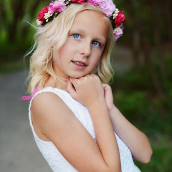 A young flower girl and junior bridesmaid wearing a pink floral head crown with ribbons