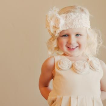 A flower girl wearing an ivory rosette flower girl dress in a 1920s style with a lace headband with a big flower