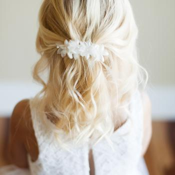 The back of a girl wearing an ivory anemone flower girl hair clip and a white lace flower girl dress with a tulle skirt.